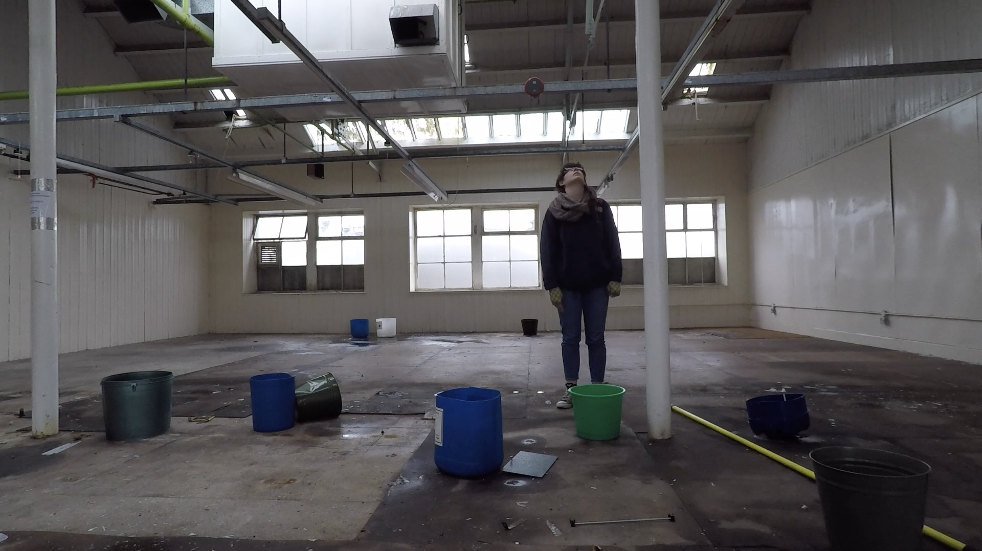Woman stares at the ceiling in a room with buckets on the floor